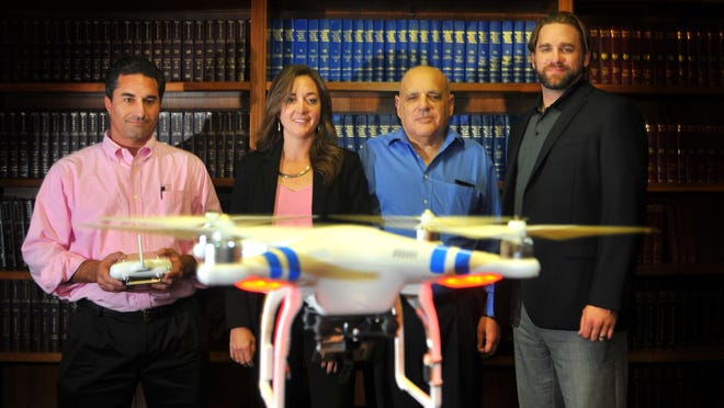 Scott Widerman, of Widerman Malek, flies a DJI Phantom drone in the law library of the firm. With him are attorneys Kelly Swartz, Edward Kinberg and Scott Jablonski. The new law basically states that you have to be a licensed pilot to fly any drone over half a pound if you are doing it for commercial purposes.