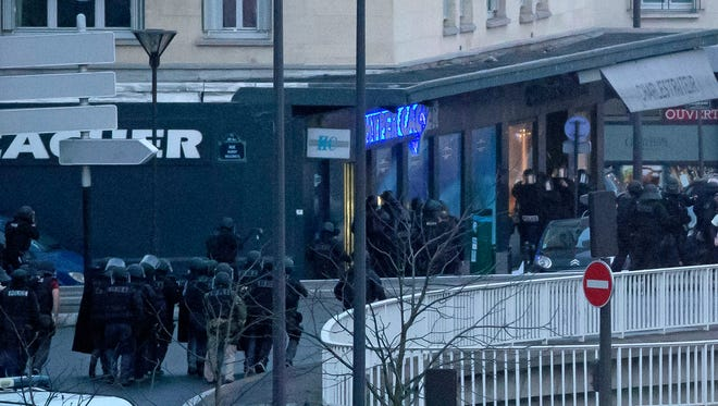 French police officers storm a kosher grocery to end a hostage situation in Paris on Jan. 9.