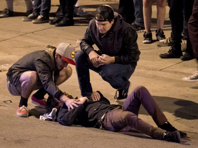 Bystanders help a man who was struck by a vehicle on Red River Street on March 13 in Austin. A man and woman were killed after a suspected drunken driver fleeing from police crashed through barricades set up for the South By Southwest festival.