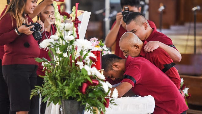 Terrence Meno, front right, is seen with other family members, as he leans over the body of his brother, Justin Roy Meno, during funeral services at the Santa Barbara Catholic Church in Dededo on Tuesday, Sept. 23, 2017.
