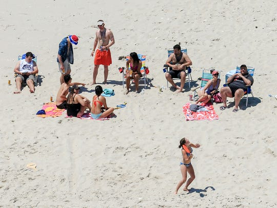 Gov. Chris Christie, right, uses the beach with his