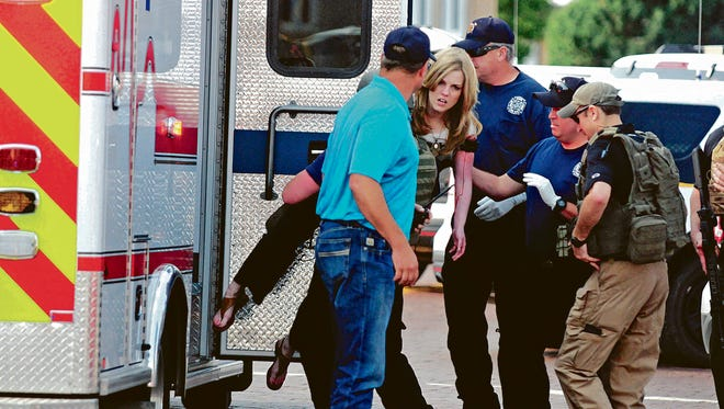 An injured woman is carried to an ambulance in Clovis, N.M., Monday, Aug. 28, 2017, as authorities respond to reports of a shooting inside a public library. A city official says police have taken a person into custody who they believe is responsible for a shooting at the library.