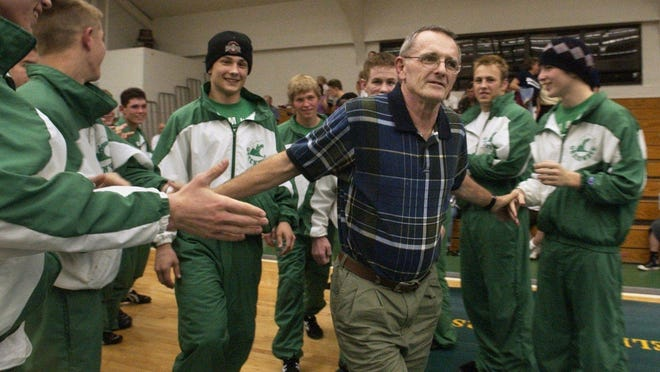 Former Fort Myers wrestling coach Gary Freis is congratulated by the Green Wave wrestling team as he is presented with an award at Fort Myers High on Feb. 4, 2003.
