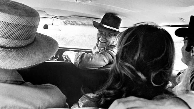 """John Wayne on the set of """"El Dorado"""" with Howard Hawks, Michele Carey and James Caan"""