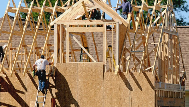 Construction crews work on a home in the Brunswick Forest neighborhood in Leland, N.C. on Oct. 6, 2014.