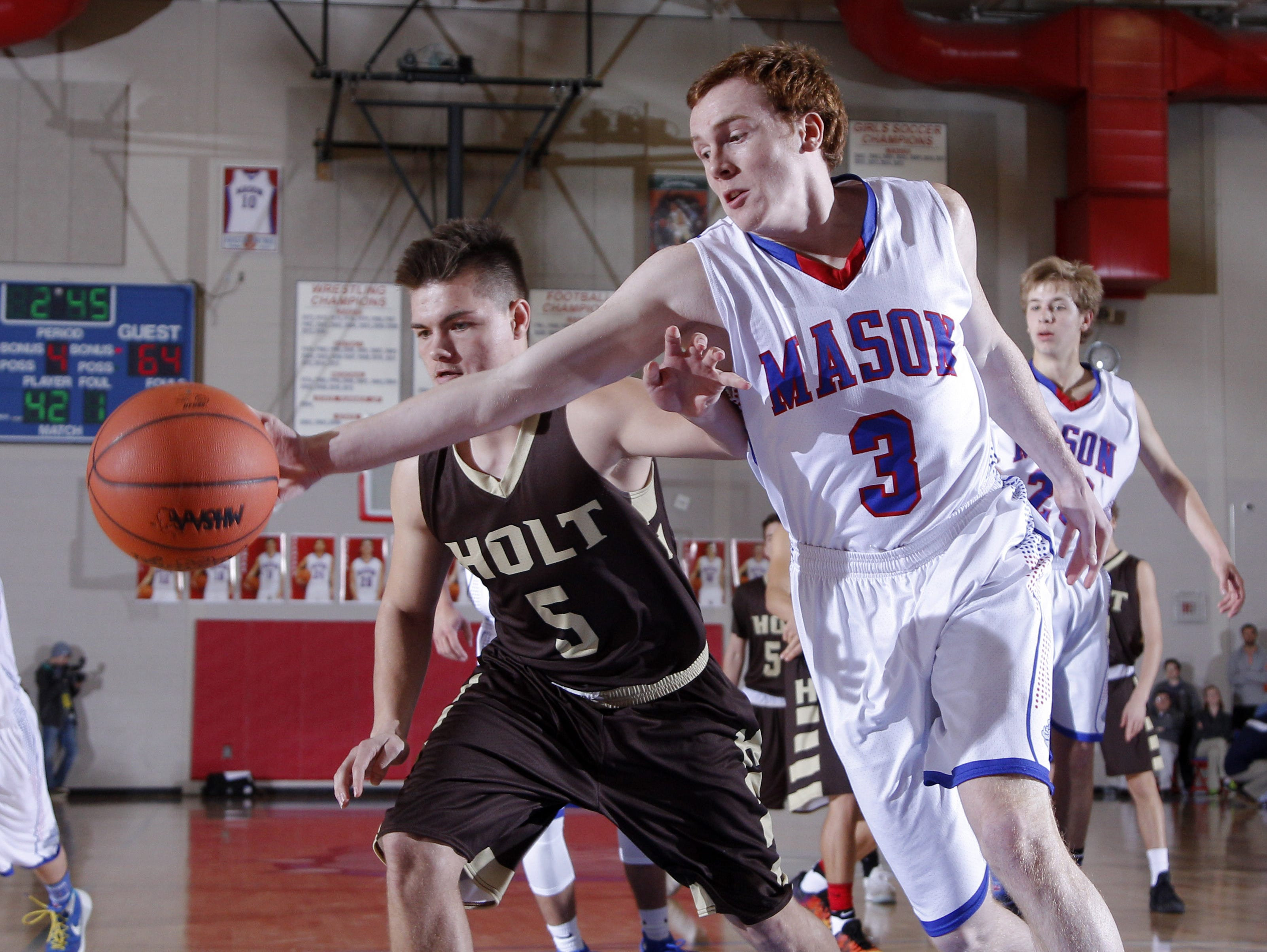 Mason's Brooks Mires (3) and Holt's Owen Brown (5) chase down the ball during their district final Friday, March 10, 2017, in Mason, Mich. Holt won 74-44.
