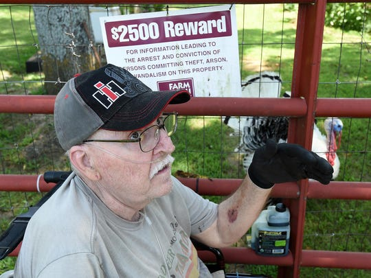 Richard Albertson sits in his wheelchair next to a sign that shows the reward being offered in the theft of tires and rims from a truck at his Gassville property.