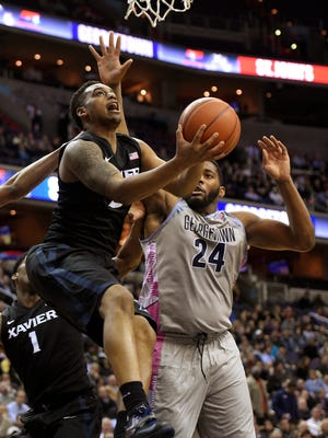 Xavier forward Trevon Bluiett, left, goes to the basket against Georgetown center Joshua Smith (24) during the first half of an NCAA college basketball game, Tuesday.
