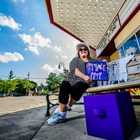 A plethora of Prince merchandise belonging to Laurie Rasmussen sits on a bench in front of the Sun Theater Tuesday July 19, 2016 in Grand Ledge.  The hat was given to Rasmussen by Prince himself at a concert.  KEVIN W. FOWLER PHOTO