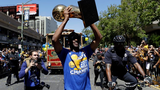 Golden State Warriors' Ian Clark holds the Larry O'Brien trophy during a parade and rally after the Warriors won the NBA basketball championship Thursday, June 15, 2017, in Oakland, Calif.