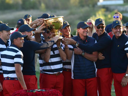The U.S. Team celebrates with the winner's trophy after the final round of the Presidents Cup golf tournament at Liberty National Golf Club in Jersey City, N.J., Sunday, Oct. 1, 2017. (AP Photo/Susan Walsh)