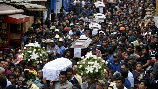 Residents carry the caskets of seven people who died in the eruption of the Fuego volcano southwest of Guatemala City on June 4, 2018.