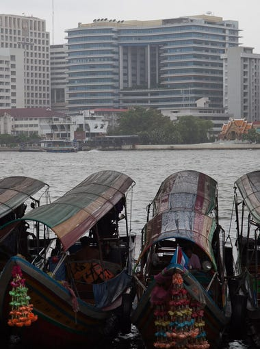 Old-fashioned boats float in front of modern buildings on Bangkok's Chao Phraya River.
