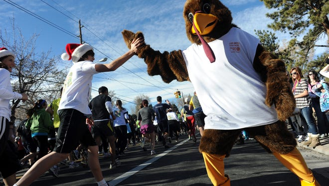 Jim Hatcher, dressed as a turkey, high fives runners at the Mile High United Way's 38th annual Turkey Trot race Nov. 24, 2011, in Denver.