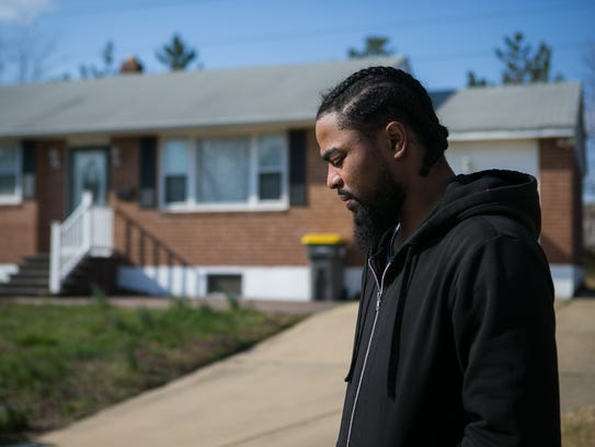 """Kashif Handy walks by one of the houses he worked on through a """"pre-apprenticeship"""" construction training program, in which trainees say they were exploited as free labor."""