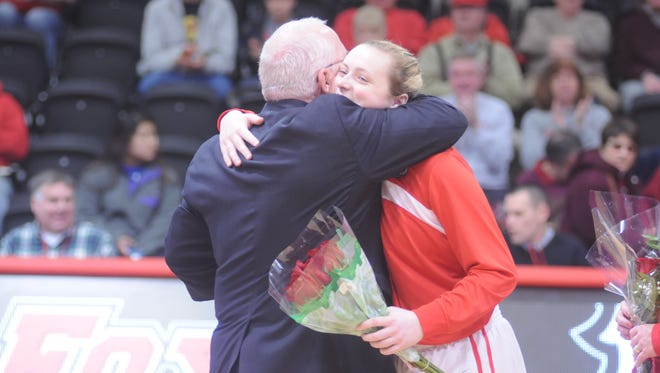 Stormville's Maggie Gallagher receives a hug from Marist women's basketball coach Brian Giorgis during the Senior Day ceremony in February 2015. The John Jay High School graduate was named Marist assistant coach.