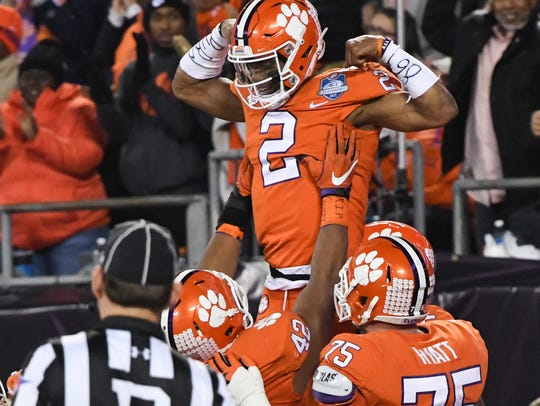 Clemson quarterback Kelly Bryant(2) is lifted by Clemson