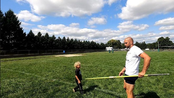 Calvin Sullins holds a javelin while his nephew, Ezra, watches as Sullins participates in a one-man decathlon.