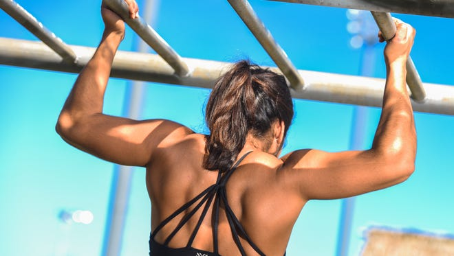 Fitness enthusiast Brianna Santos, 24, flexes her back muscles while hanging from the hand-over-hand bars at the Paseo in Hagåtña on Thursday, Nov. 10, 2016.