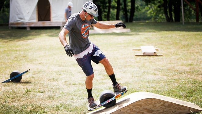 Josh Aldridge rides a OneWheel over an obstacle June 23 at Southern Raft Supply in Woodfin.
