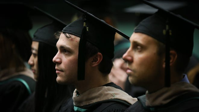 Adam Barnhart, center, looks on as his graduating class is addressed during the CSU College of Business Commencement Ceremony on Saturday, December 17, 2016, in Fort Collins.