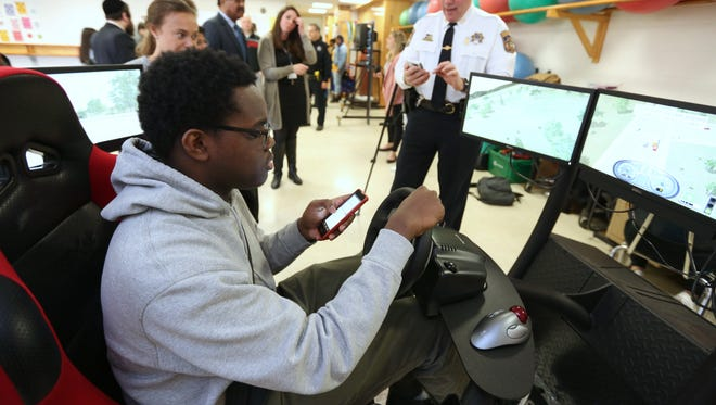 Ramapo High School student Kristof Philippe operates a driving simulator while taking a text from Rockland County Sheriff's Office Chief William Barbera, right, at Ramapo High School March 28, 2018.