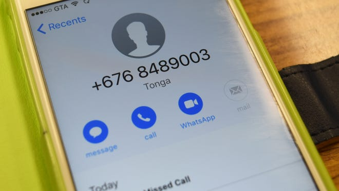 A phone number from Tonga is displayed on an iPhone. Residents have been receiving a similar call, which is being flagged as a phone scam.