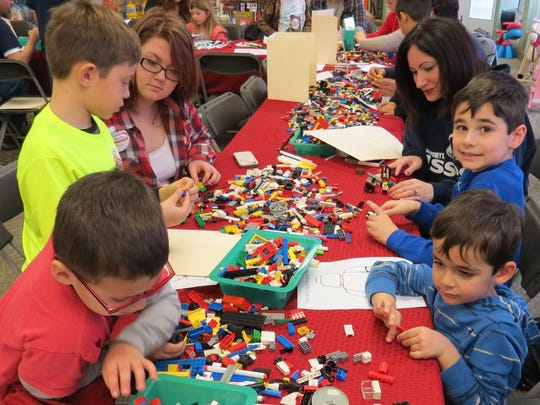 Billy Nees, 6, Joey Mott, 8, and Hannah Nees, 16, work on their Legos across the table from Nate Fredericks, 4, Cole Fredericks, 7, and Mandy Fredericks during Lego March Madness at Toy Market in downtown Hammonton.