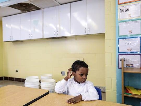 Dean Hayes, 5, of Detroit sits at his desk that is
