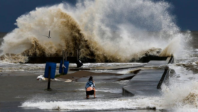 Sydney Schultz takes photos of waves crashing next to Rollover Pass as Tropical Storm Cindy approaches the coast Wednesday, June 21, 2017 on the Bolivar Peninsula. (Michael Ciaglo /Houston Chronicle via AP)