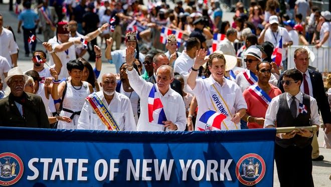 New York Governor Andrew Cuomo, lower right, marches at the front of the Dominican Day Parade in New York Sunday, Aug. 10, 2014.