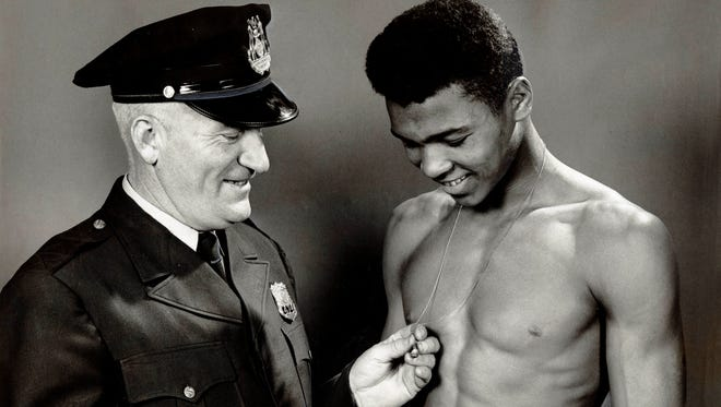 In this March 29, 1959, file photo, policeman and mentor Joe Martin congratulates Muhammad Ali as he admires his Golden Gloves ring.