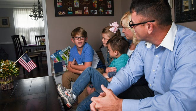 John Michael Tripp, left, 9, the oldest of three children of U.S. Army National Guard Staff Sgt. Allen Tripp, right, and Christy, talks about the excitement of seeing his father come home, during an interview in their Anderson home on August 8.