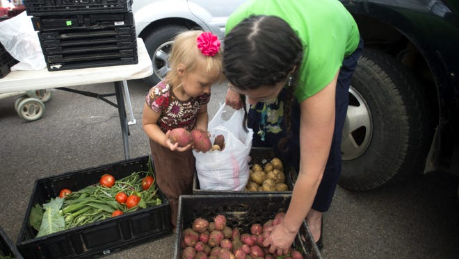 Annie Nelson and AnneMarie Nelson pick out potatoes at a past Larimer County Farmers Market.
