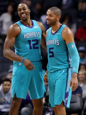 Charlotte Hornets center Dwight Howard (12) and guard Nicolas Batum (5) smile in the closing seconds after their win over the LA Clippers during the second half at Spectrum Center.