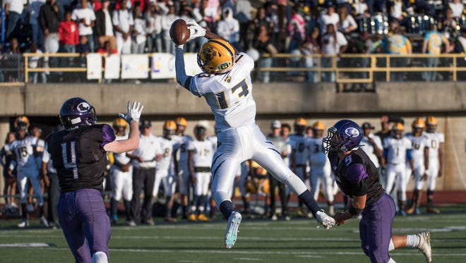 Battle Creek Central's Darrell Banks (13) leaps for the reception during first half action against Lakeview Friday evening