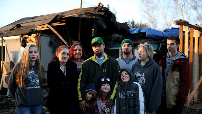 Jennifer and Jason Craig, center, with their children, from left, Raina Rush, 12, Misty Watson, 20, Jalena Craig, 4, Jazlynne Craig, 6, Julian Craig, 8, Tristan Watson, 19, Tarah Hewitt, 16, and Nolan Hewitt, 14, stand in front of their Keizer home that was destroyed by a fire on Saturday. Photographed on Wednesday, Dec. 13, 2017.