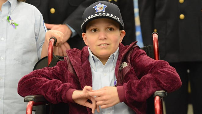 Emily Beazley is photographed after she and her sister Olivia are made honorary police officers at the Public Safety Building, Tuesday, April 28, 2015, in Chicago.