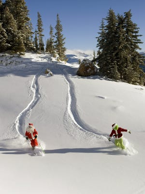 Santa and Grinch characters ski at Crested Butte Mountain Resort.