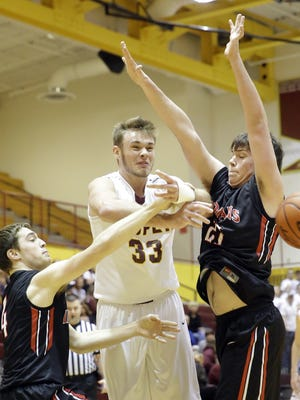 Cooper's Colin Hathorn loses the ball after being surrounded by Holy Cross players Tyler Bezold (right) and Hamilton Scott.