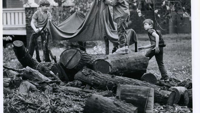 Three Springfield boys (left to right) Chris Wilcox, 7, Jason Baumgartner, 8, and Mark Anderson, 10, work to build a fort around a fallen tree on Cherry Street in November of 1985.