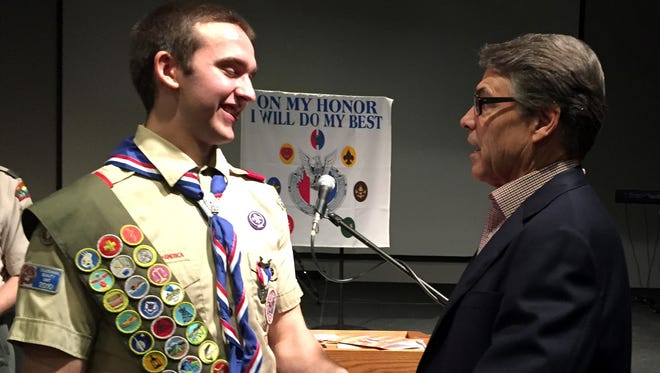 Eagle Scout Daniel Rosenthal, 18, of Cedar Rapids, is congratulated by former Texas Gov. Rick Perry after an Eagle Scout Court of Honor on Saturday. Perry, who earned his Eagle Scout rank as a youth in Paint Creek, Texas, shook hands with the young man using the left-handed Boy Scout handshake, which is made with the hand nearest the heart and is offered as a token of friendship.