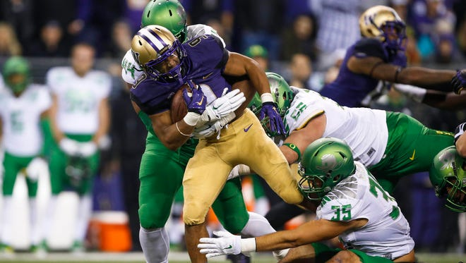 Oct 17, 2015; Seattle, WA, USA; Washington Huskies fullback Myles Gaskin (9) is tackled by Oregon Ducks defensive lineman DeForest Buckner (44), defensive lineman Alex Balducci (56) and linebacker Kaulana Apelu (39) during the second quarter at Husky Stadium. Mandatory Credit: Jennifer Buchanan-USA TODAY Sports