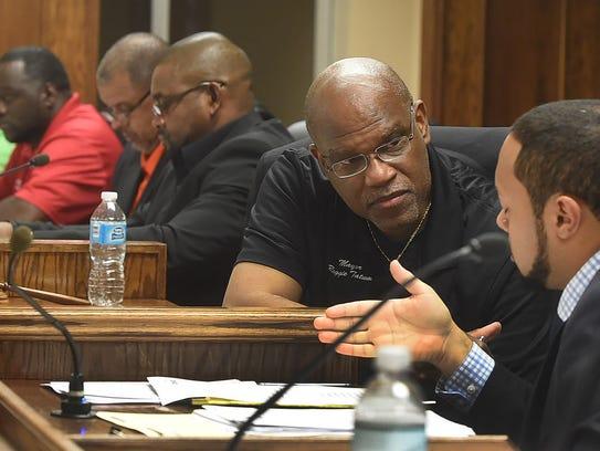 Mayor Reggie Tatum confers with the city attorney during