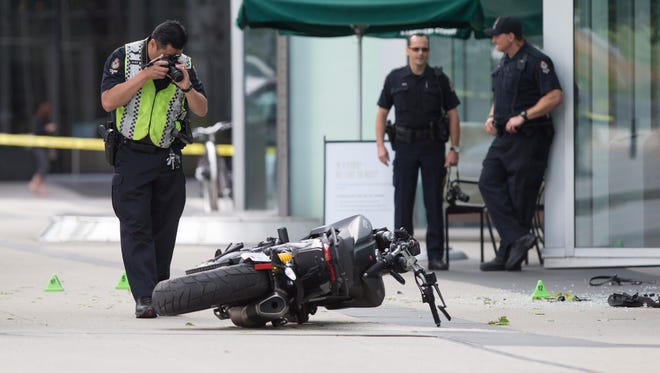 A police officer photographs a motorcycle after a female stunt driver died working on the movie 'Deadpool 2' in Vancouver.