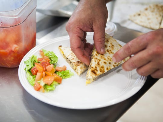 Chris Rose, a cook at Take Out 250 in Fishersville, places slices of a cheeseburger quesadilla on a customer's plate during lunch at the restaurant on Tuesday.