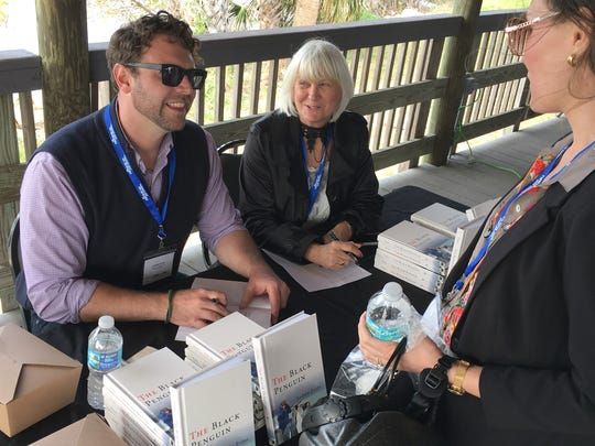 """Keynote speaker Andrew Evans, a National Geographic Travel journalist and television host, sign copies of his memoir, """"The Black Penguin,"""" at Manatee Sanctuary Park in Cape Canaveral. He is joined by Bonnie King, deputy director of the Space Coast Office of Tourism."""