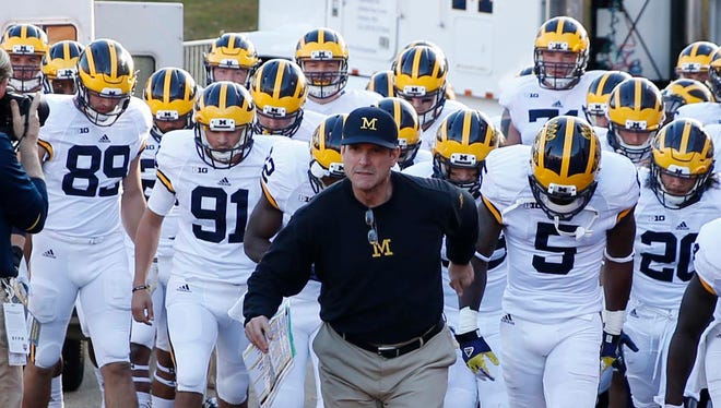 Nov 14, 2015; Bloomington, IN, USA; Michigan Wolverines coach Jim Harbaugh leads his team onto the field before the game against the Indiana Hoosiers  at Memorial Stadium.