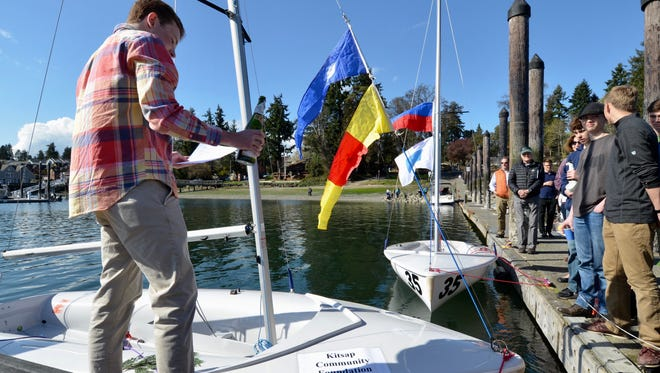 Bainbridge senior captain Harry Saliba christens a new 420E sailboat partially underwritten by the Kitsap Community Foundation during a ceremony Saturday, April 15, 2017, at the Waterfront Park public dock at Bainbridge Island. Six new sailboats were purchased by the Friends of Bainbridge Island High School Sailing (FOBIHSS).