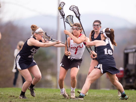 A trio of Essex defenders collaps on Champlain Valley's Lydia Maitland, center, during a girls lacrosse game in Hnesburg on Friday, May 4, 2018.